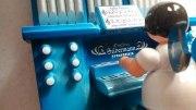 Engel mit blauen Flügeln sitzt an der Orgel mit Spieluhr